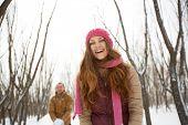 Portrait of happy girl in winterwear laughing on background of her boyfriend outside