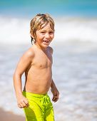 Young happy boy having fun on tropical beach