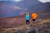 Fitness sport couple jogging outside, training together outdoors. Running on amazing trail at sunset, Dramatic beautiful volcano landscape