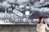 Composite image of elegant businesswoman holding black umbrella against white background