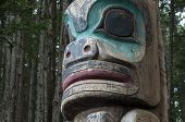 image of totem pole  - Closeup of face of wooden Tlingit totem pole in dense pine forest in Sitka Alaska - JPG