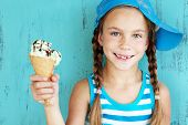 stock photo of 7-year-old  - Portrait of 7 years old kid girl eating tasty ice cream over blue - JPG