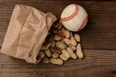 A bag of peanuts and a baseball on an old wooden bench at the ballpark. The paper bag is on its side with the nuts spilling out.  Horizontal format with copy space.