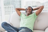 Portrait of a relaxed young Afro man with headphones sitting on sofa in a bright house