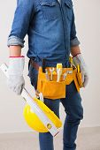 Mid section of a handyman with toolbelt around his waist and hard hat