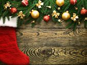 stock photo of christmas bells  - Christmas fir tree and christmas sock with decoration on a wooden board - JPG