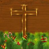 Merry Christmas celebration concept with golden wooden Christian Cross on green grass background with little Xmas trees.