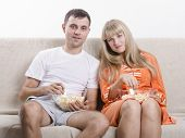 Young couple sitting on the couch, eating popcorn and watching TV