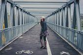 pic of girl walking away  - Pretty girl with long hair walking away on a bridge - JPG