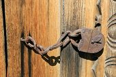 Old rusty lock on wooden door