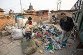 KATHMANDU, NEPAL - DEC 19, 2013: Unidentified people from poorer areas working in sorting of plastic