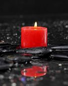 pebbles and red candle on wet background