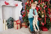 Little boy rides on rocking horse in room near decorated christmas tree