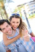 Cheerful girl on boyfriend's back showing thumbs up