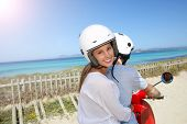 Cheerful girl riding moto with boyfriend by the beach