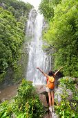 Happy hiker - Hawaii tourists hiking by waterfall. Woman cheering during travel on the road to Hana