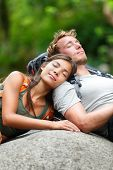 Hiking couple lovers relaxing sleeping in nature. Tried hikers resting lying down outdoors taking a