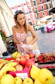 Young woman buying fruits from organic market