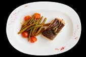 Cod fillet with runner beans isolated on black background