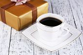 Cup of coffee and gift on wooden table close-up