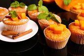 Tasty pumpkin muffins on dark background