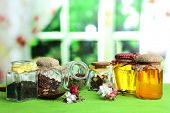 Assortment of herbs and tea and honey in glass jars on wooden table, on bright background
