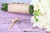 Beautiful wedding bouquet and rings on wooden background