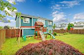 picture of chute  - Small fenced backyard with playground for kids with chute swings and climbing board - JPG