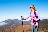 Female hiker with backpack standing on mountain top enjoying the view