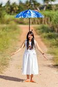 Beautiful young Thai girl balancing an open blue umbrella on her head as she stands on a rural path