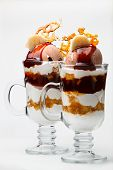 picture of dainty  - Caramel and chocolate parfait dessert with whipped cream and ice cream topped with crispy caramel and served in tall glasses for a gourmet dessert - JPG