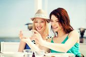 summer holidays and vacation - girls taking photo in cafe on the beach