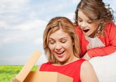 family, child, holiday and party concpt - smiling mother and daughter with gift box
