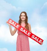 beauty, fashion, shopping and happy people concept - young woman in dress with sale sign