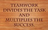 Teamwork divides the task and multiplies the success - quote by unknown author on wooden red oak bac