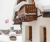 picture of chalet  - Swiss chalet during heavy snow with Swiss flag in background - JPG