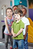 Group of interracial children in a row in a kindergarten room