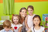 Portrait of children with happy nursery teacher in a kindergarten