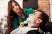 Female Barber Shaving A Man