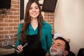 stock photo of barber razor  - Gorgeous female barber holding a razor and about to shave a man in a barber shop - JPG