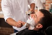 stock photo of barber  - Barber putting some shaving cream on a client before shaving his beard in a barber shop - JPG