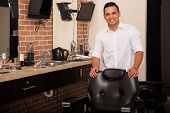 image of shaving  - Handsome young barber standing behind a barber chair and greeting clients with a smile - JPG