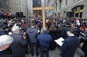 Firefighter John Bartlet holds cross before faithful at Ground Zero