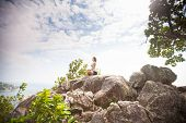 stock photo of samadhi  - Yoga meditation in lotus pose by woman on the peak of mountain