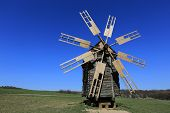 old wooden windmill on meadow in Pirogovo open-air museum, Kiev, Ukraine