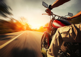 stock photo of biker  - Biker riding motorcycle  on an empty road at sunny day - JPG