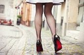 stock photo of fishnet  - Woman with legs wearing fishnet stockings and black high heel shoes - JPG