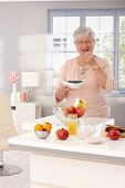 Elderly lady eating blueberry, smiling happy, looking at camera.