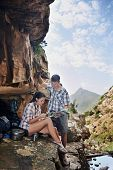 A couple taking a break from their hiking trail and looking at a map with copyspace