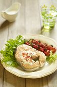 Baked salmon with red caviar sauce, cherry tomatoes and fresh salad